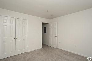 Carpeted bedroom with double door closet
