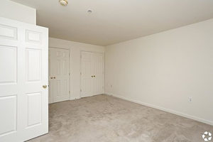 Carpeted bedroom with two double door closets