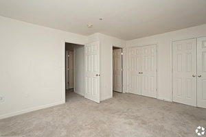 Carpeted bedroom with two double door closets, doors leading to hallway and bathroom