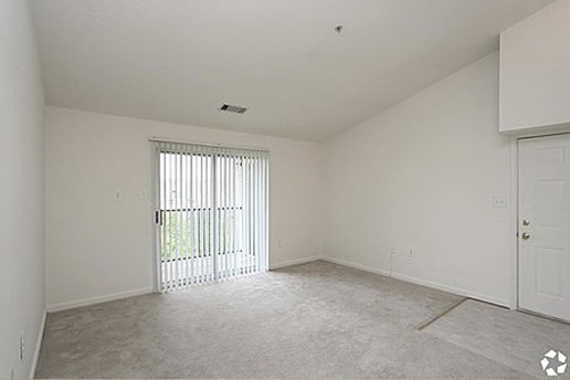 Carpeted living area with sliding glass door leading to balcony