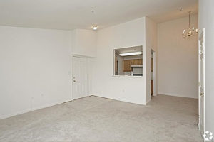 Carpeted living area with tall ceilings, cutout into wall viewing the kitchen