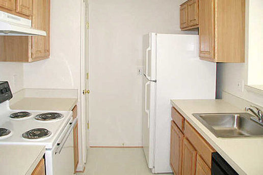 Kitchen with pantry, fridge, electric stove top oven, sink and cabinets