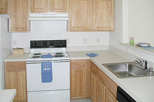 Kitchen with electric stove top oven, sink and cabinets