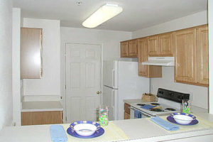 Kitchen with pantry, electric stove top oven, fridge, sink and cabinets. Placemats set on counter