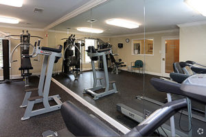 Gym with workout machines and mirrored back wall