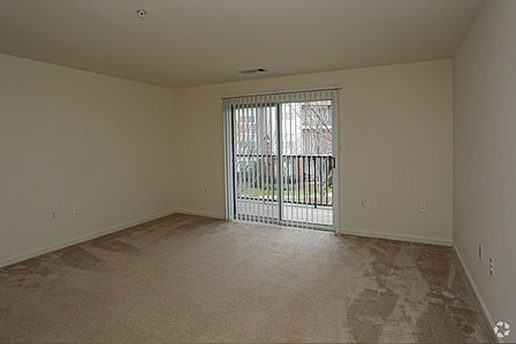 Carpeted living area with sliding glass doors leading to balcony