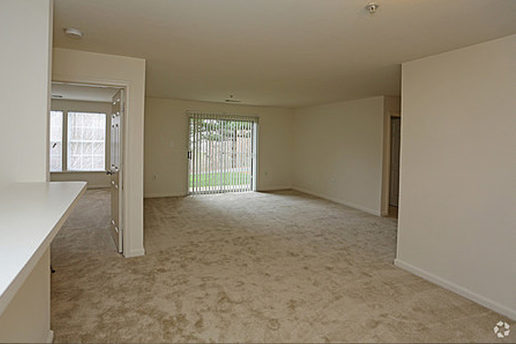 Carpeted living area showing view into living room and bedroom