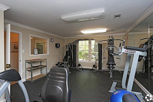 Gym with several workout machines with window on back wall
